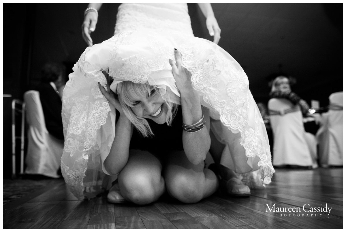 woman under bride's dress having fun at reception photo