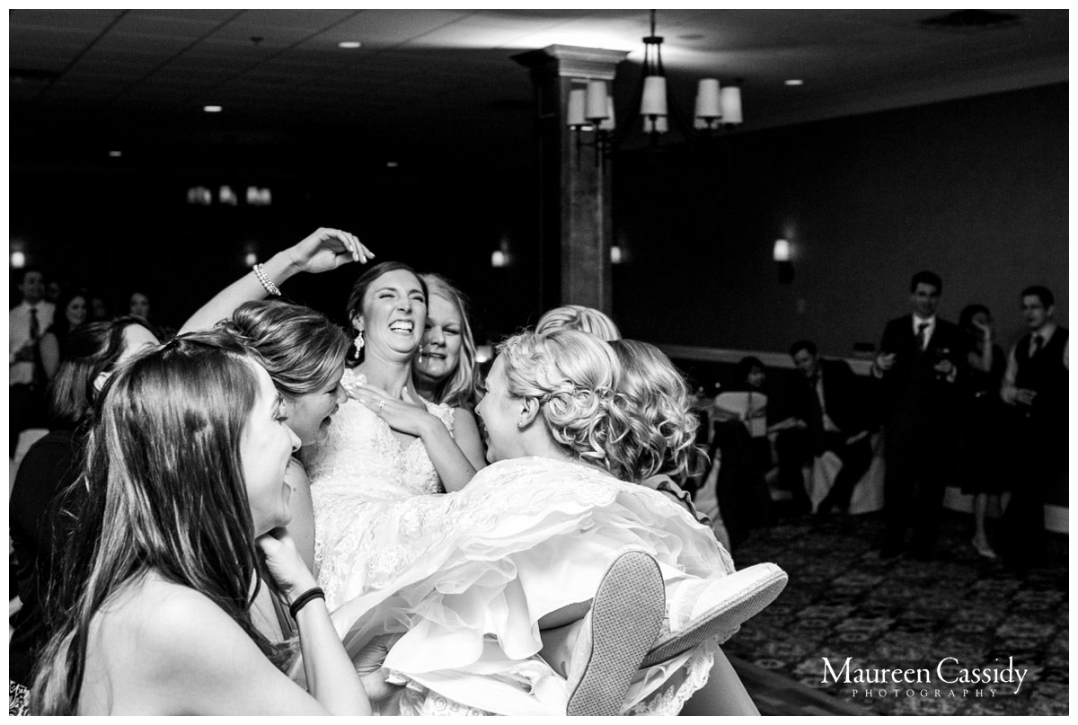bridesmaids carrying bride at reception photo