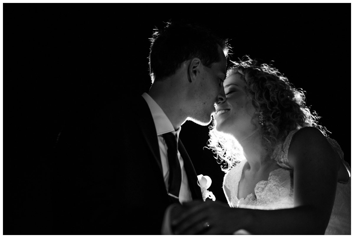 newlyweds kissing happy outside black and white
