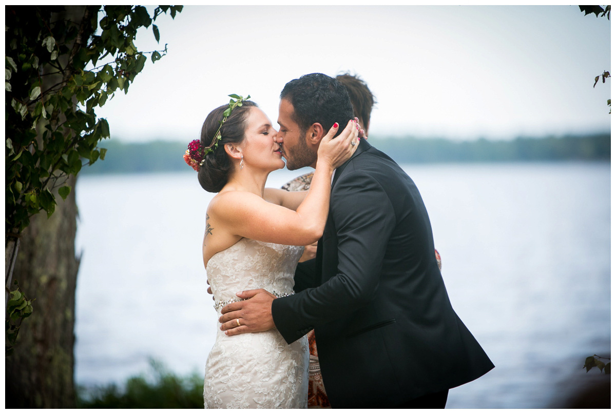 first kiss at rustic wedding in backyard