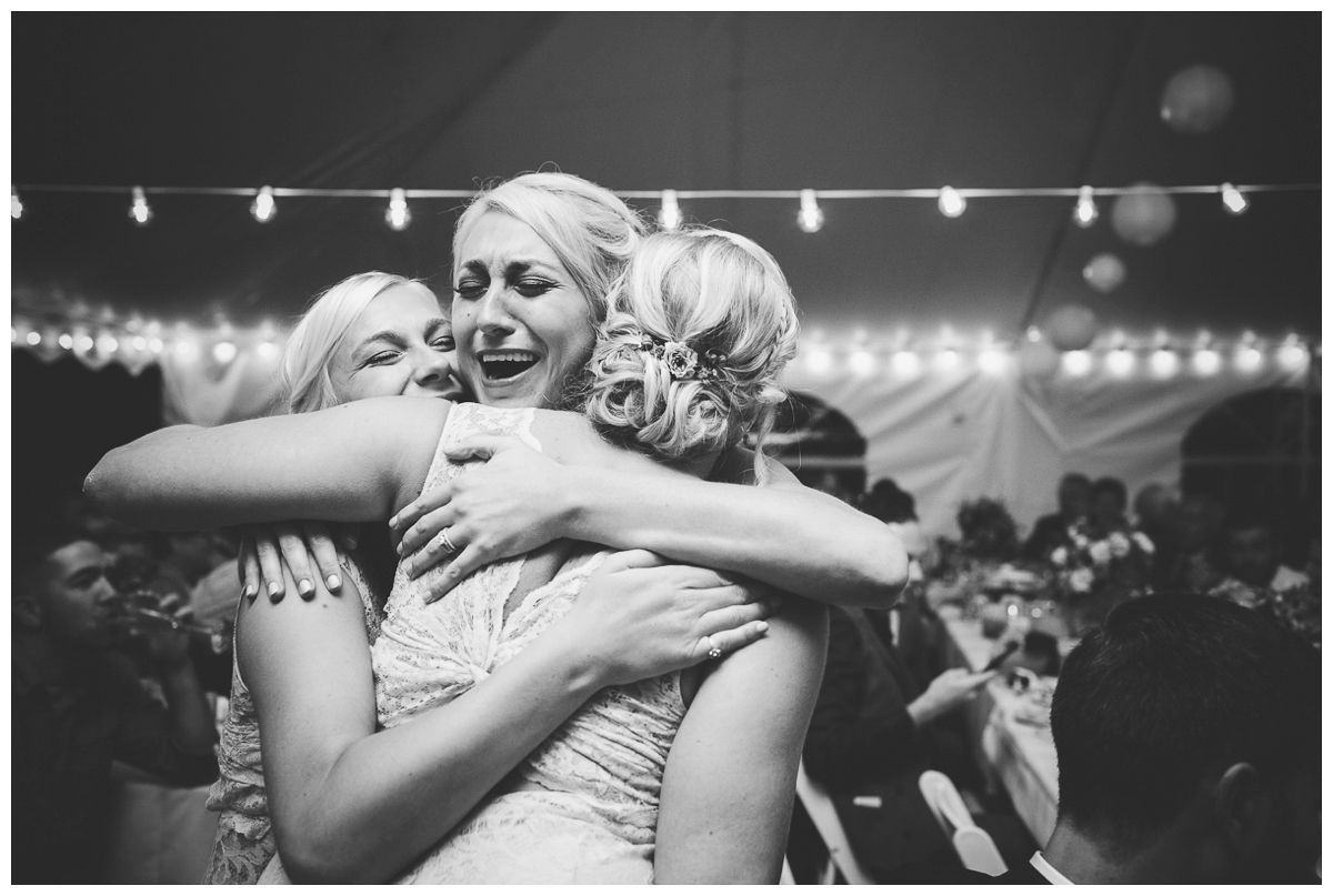 bride and bridesmaids hugging photo
